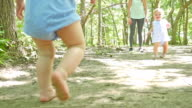 Toddler girls playing together, walking barefoot at park with mom