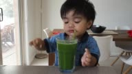 Toddler is drinking green smoothie from a straw