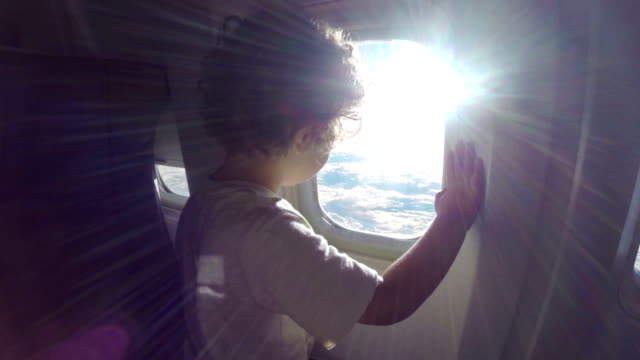 Toddler is watching panorama through window airplane