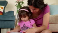 Toddler Reading with Mom on Her Lap