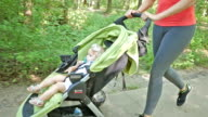 Toddler riding in jogging stroller as mom goes for run in park