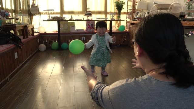 Toddler walking towards young mother
