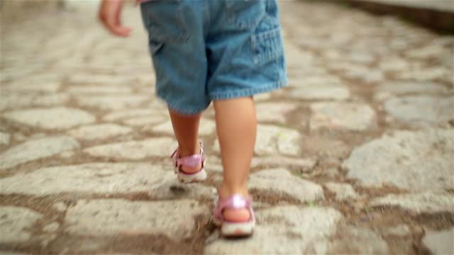 Toddler's feet walk down cobblestone-street in third-world country