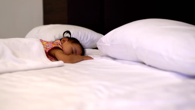 Todler girl (2-3) sleeping on bed