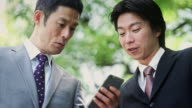 Tokyo Businessmen Looking at Phone