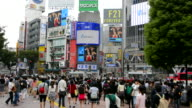 Tokyo Japan crowds rush moving walking in the busy Shibuya Station area of Shilbuya Crossing with locals rushing everywhere in downtown crowded streets and sidewalks crossing
