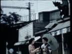 WS MS TU PAN Tokyo shopping street near electric elevated train, historical town of Kamakura, Three temple maidens in traditional dresses at Hachiman Shrine feeding pigeons / Tokyo, Japan / AUDIO
