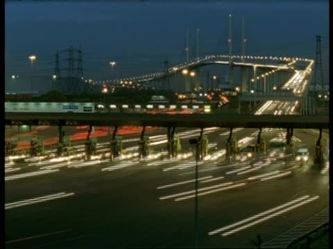 T/L WA Toll booths at end of toll bridge, Dartford, streaky traffic, evening