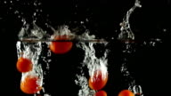 SLOW MOTION: Tomatos Splashing into Water