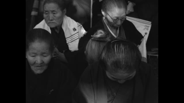 CU toothless old man seated in crowd of people bowing / MS kneeling crowd / crowd raise paper flags cheer / elder women in crowd bow heads as if in...