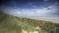 Angled WS Dunes covered in Marram grass next to beach North Sea dots of people moving near water's edge low cloud over ocean water Sites of Special...