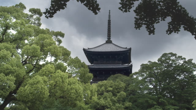 MS Top of five-story pagoda of To-ji temple with trees in foreground against cloudy sky, Kyoto, Japan