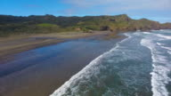 Top view of Piha Beach with coast waves hitting on shore.