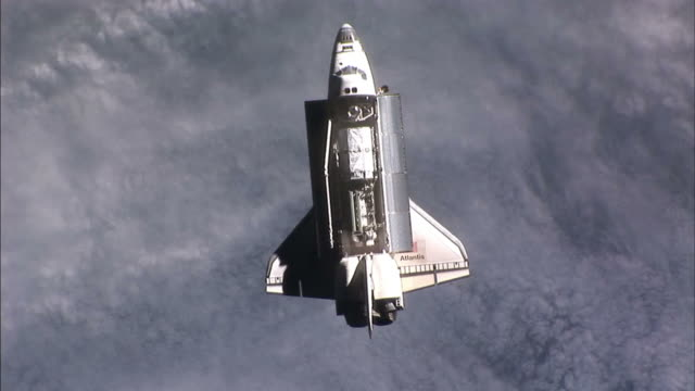 Top view of Space Shuttle Atlantis as seen from the International Space Station the earth below it View of Space Shuttle Atlantis over the Earth