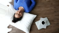 Top view of woman lying down listening music on the wood floor with cup of coffee, Lifestyle concept