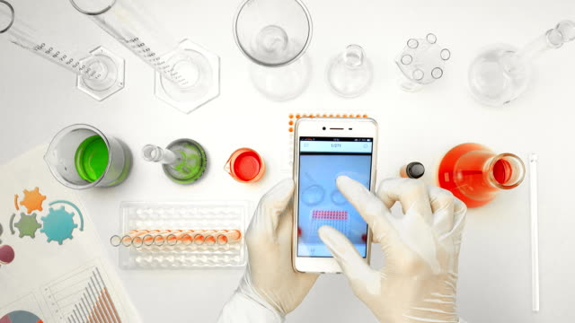 top view scientist using smart phone in laboratory