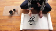CU Top View Young woman writing chinese calligraphy artwork in  studio