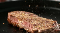 SLO MO Topping a thick beef steak with seasoning
