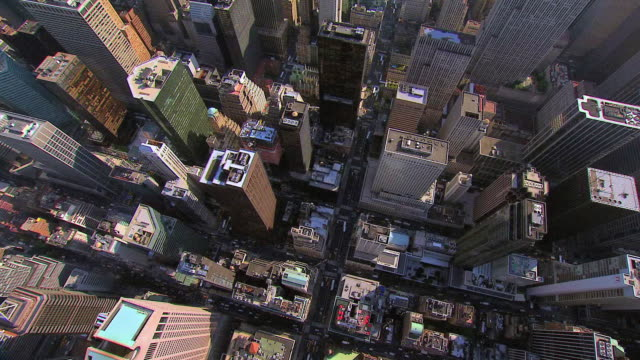 AERIAL Tops of skyscrapers and buildings, with city streets between and dots of green spaces / New York City, New York, United States