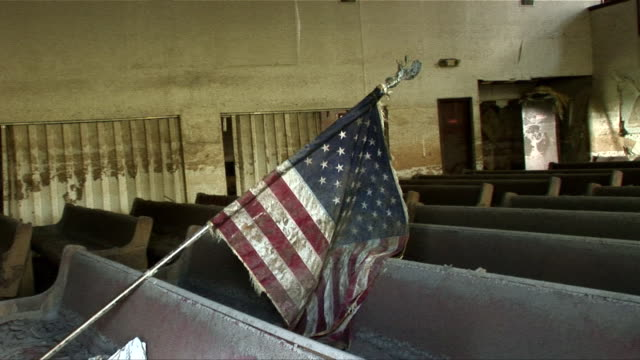 CU ZO Torn bible sitting on muddy pew with dirty American flag leaning over it in Ninth Ward church/ New Orleans, Louisiana
