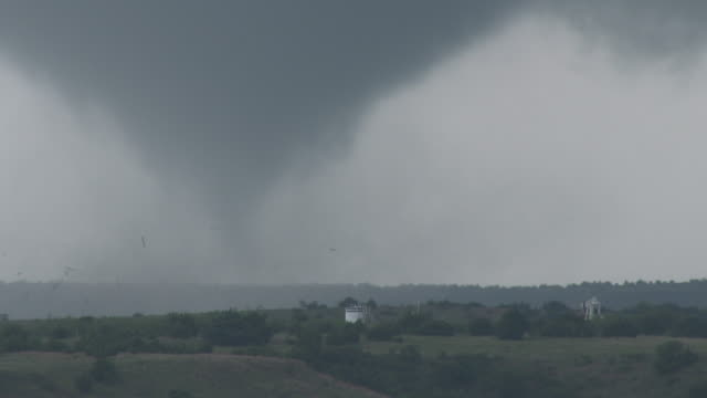 Tornado Hitting A Structure, And Throwing Debris Into The Air