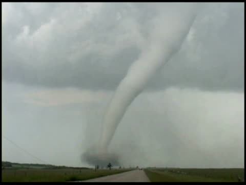 WA Tornado moving over countryside, Storm chasers car drives towards it, USA