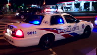 Toronto, Canada: Police car stopped in city corner at night. They have a stopped car in the intersection