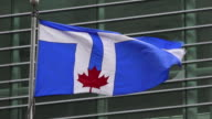 Toronto city flag with its blue and white colors and maple leaf waving or flying in the downtown, Canada