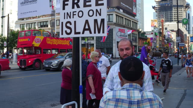 Toronto,Canada: Different religions in Yonge-Dundas Square. Islam and Christianity contrast.  The famous and crowded place is used to preach the different religions in the multi cultural Canadian city capital of the province of Ontario