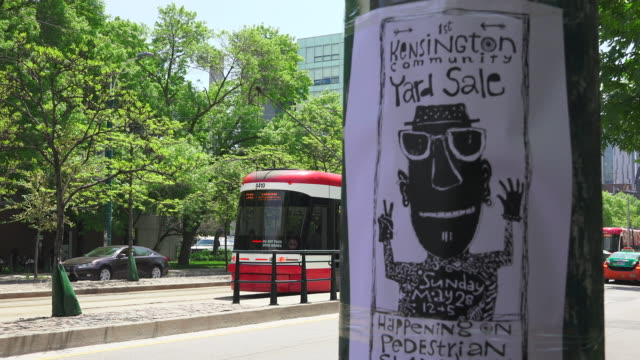 Toronto,Canada: Kensington Market First Community Yard Sale advertisement in Spadina Avenue. Modern Bombardier Flexity Outlook and everyday lifestyle in the Canadian city.