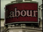 Tory Party advertising campaign ITN London CMS Women pointing at sign in street LALMS Large neon sign on top of building 'Tories Back New Labour'...