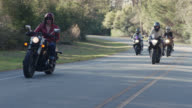 SLO MO. Tough girl in leather jacket leads the pack as group of women on motorcycles cruise down sunny highway.