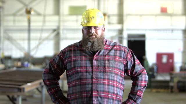 Harter Mann mit Bart und Bauarbeiterhelm geht in Richtung Kamera