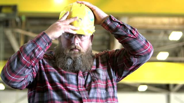 Harter Mann mit Bart setzt auf Bauarbeiterhelm