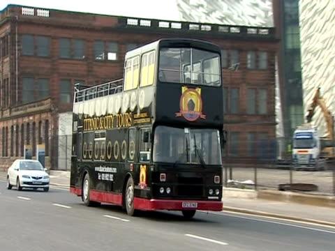 A tour bus passes the Titanic Belfast museum