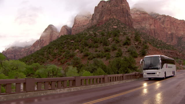 Tour bus passing camera in Zion National Park with wet road and clearing storm
