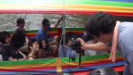 A tour group boards a boat at the Taling Chan Floating Market in Bangkok