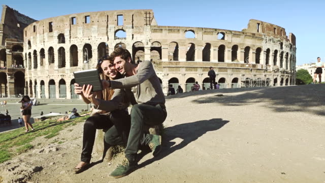 Tourist couple taking a selfie in front of the Coliseum