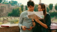 Tourist couple with a map by the Roman forum in Rome