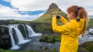 Tourist in Iceland taking pictures of Kirkjufellsfoss waterfall