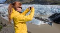 Tourist in gelben Regenmantel fotografieren der Gletscher