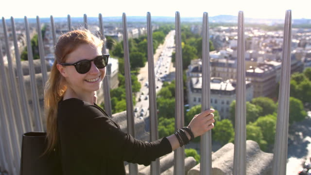 Tourist on top of Arc de Triomphe in Paris overlooking the city, smiling into camera