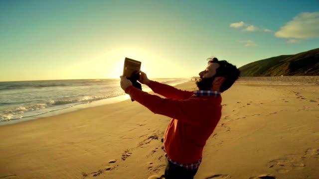 WS Touristen Fotografieren mit digitalen Tablet am Strand von Malibu