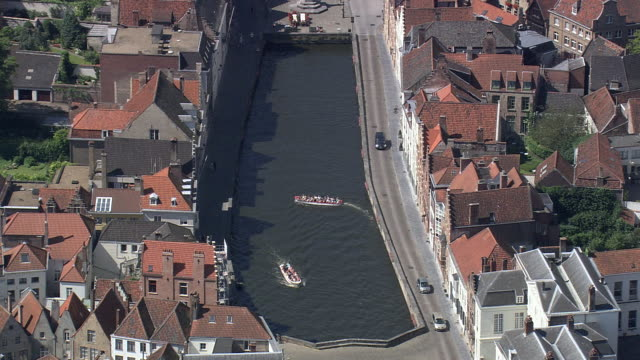 MS AERIAL ZI ZO PAN Tourist roaming through boat in Bruges canal in city / Flanders, Belgium