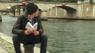 WS ZO Tourist sitting by river reading book and walking away, Paris, Ile de France, France