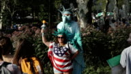 Tourist takes photo with Statue of Liberty in Battery Park, New York City