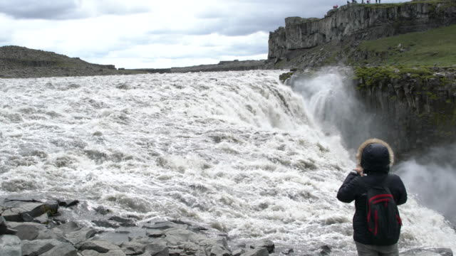 A tourist taking photo of the  Dettifoss  waterfall  in Vatnajökull National Park, Iceland  in summertime