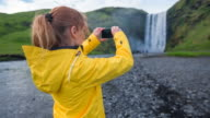 Tourist taking pictures of Iceland's waterfall Skogafoss