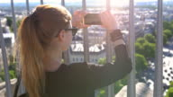Tourist taking pictures of Paris from top of Arch of Triumph