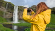 Tourist taking pictures of waterfall